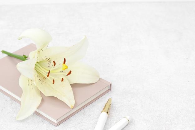 Weiße lilie auf rosa notizbuch mit stift