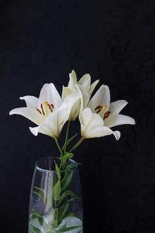 Weiße lilie blüht blumenstrauß auf schwarzem hintergrund.