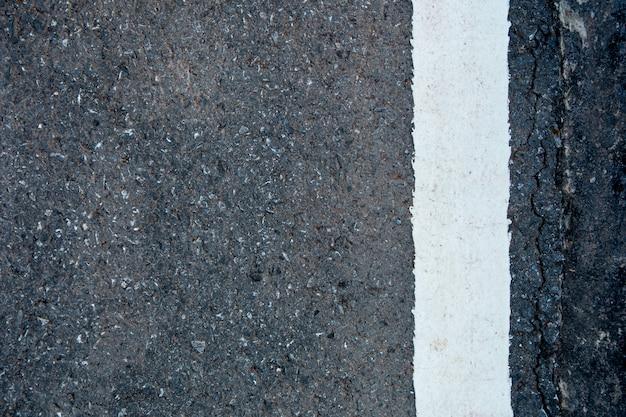 Weiße linie auf schwarzem asphaltstraßenhintergrund mit kopienraum