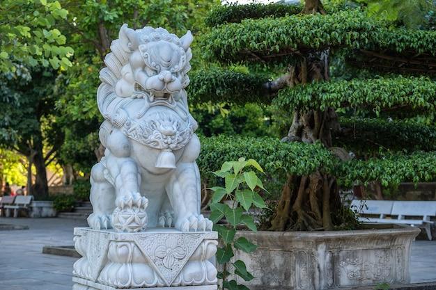 Weiße löwenstatue des marmors im naturpark im tropischen garten, vietnam. nahansicht