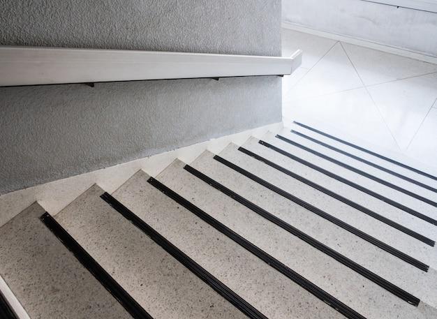 Weiße marmortreppe mit der metallschiene.