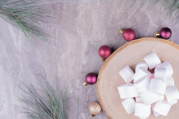 Weiße marshmallows auf holzbrett mit weihnachtskugeln herum.