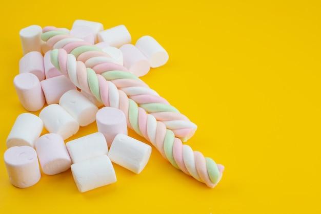 Weiße marshmallows der vorderansicht süß auf gelb