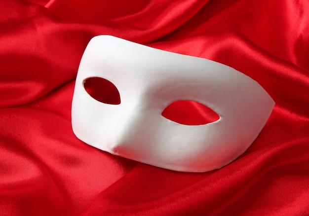 Weiße maske auf rotem seidenstoff
