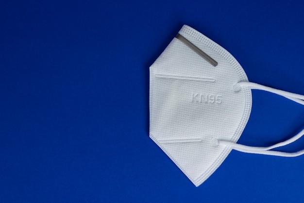 Weiße maske kn95 oder n95 mit antiviraler medizinischer maske zum schutz vor coronavirus auf blau