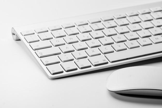 Weiße maus und tastatur eines personalcomputers auf einem weißen hintergrund