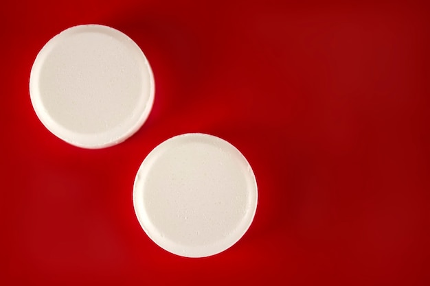 Weiße medikamentenpillen liegen auf rotem grund. medizin, pharmazie und gesundheitswesen. leerer platz für text.
