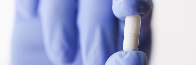 Weiße medizinische kapsel wird vom arzt in einem handschuh gehalten
