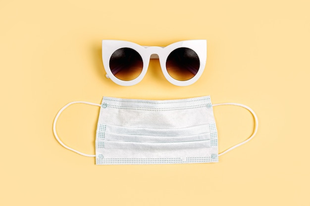 Weiße medizinische maske und sonnenbrille auf gelbem hintergrund. gesichtsmaske zum schutz vor viren, grippe, coronavirus, covid-19. medizinische ausrüstung.