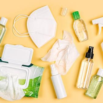 Weiße medizinische masken und atemschutzmasken mit antibakteriellen feuchttüchern, desinfektionsspray und händedesinfektionsmittel auf gelbem hintergrund. persönliches hygieneprodukt zum schutz vor viren, grippe, coronavirus, covid-19
