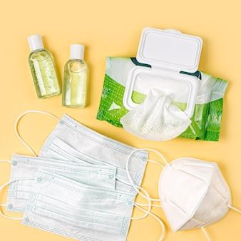 Weiße medizinische masken und atemschutzmasken mit antibakteriellen feuchttüchern und händedesinfektionsmittel auf gelbem hintergrund. persönliches hygieneprodukt zum schutz vor viren, grippe, coronavirus, covid-19