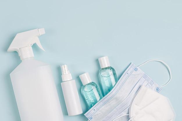 Weiße medizinische masken und atemschutzmasken mit händedesinfektionsmittel auf blauem hintergrund. gesichtsmaskenschutz kn95 oder n95 und chirurgische masken zum schutz vor viren, grippe, coronavirus, covid-19.