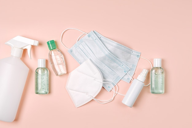 Weiße medizinische masken und atemschutzmasken mit händedesinfektionsmittel auf rosafarbenem hintergrund. gesichtsmaskenschutz kn95 oder n95 und chirurgische masken zum schutz vor viren, grippe, coronavirus, covid-19.