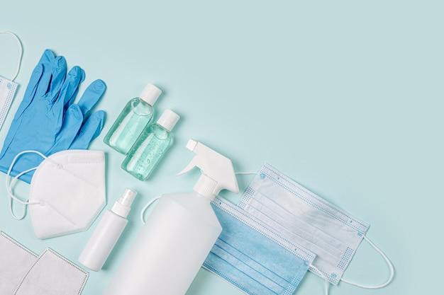 Weiße medizinische masken und atemschutzmasken mit handschuh, handdesinfektionsmittel auf blauem hintergrund. gesichtsmaskenschutz kn95 oder n95 und chirurgische masken zum schutz vor viren, grippe, coronavirus, covid-19.