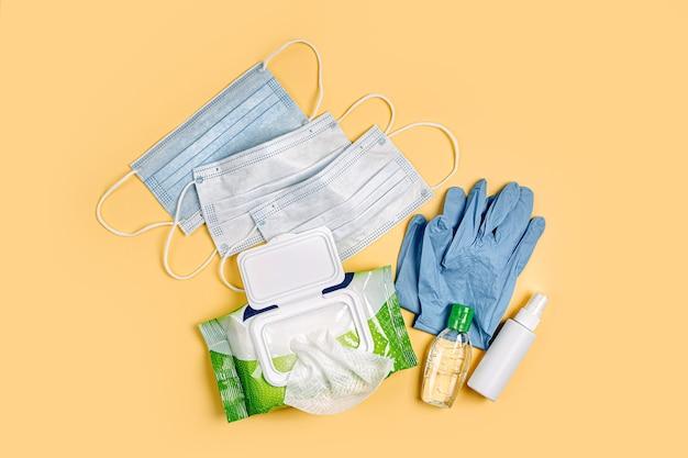 Weiße medizinische masken und handschuhe mit antibakteriellen feuchttüchern und händedesinfektionsmittel auf gelbem hintergrund. persönliches hygieneprodukt zum schutz vor viren, grippe, coronavirus, covid-19
