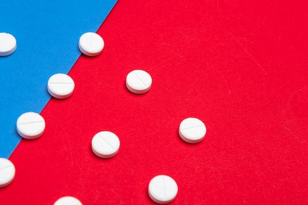 Weiße medizinische pillen auf zwei färben rot und blau