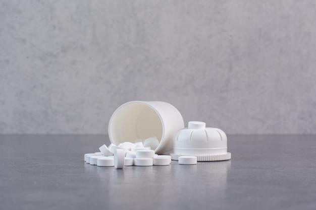 Weiße medizinische pillen aus plastikbehälter.