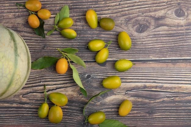 Weiße melone und frische kumquatfrüchte auf holztisch.