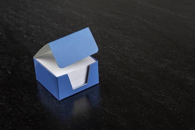 Weiße memopapiere in einer box auf dunklem hintergrund