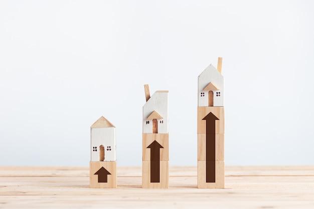 Weiße miniaturhäuser auf holzklotz mit wachstumspfeilzeichen