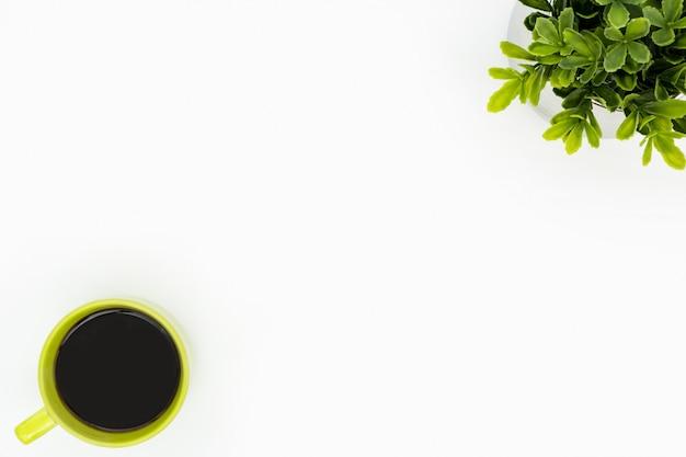 Weiße minimale schreibtischtabelle mit grüner kaffeetasse und baumtopf.