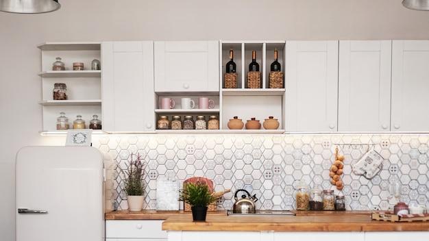 Weiße moderne küche. eine mischung aus rustikalem, skandinavischem und modernem stil. realistische küche - lage in einem fotostudio.