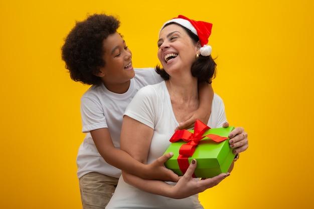 Weiße mutter mit dem schwarzen sohn, der geschenke am weihnachtsabend austauscht. pflegekind sozialer respekt, hautfarbe, inklusion.