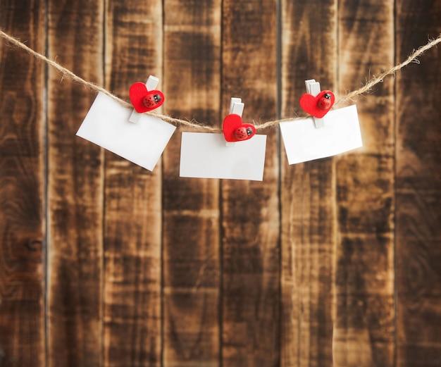Weiße noten an einem seil mit einer wäscheklammer verziert mit einem holzherz auf einem holzhintergrund