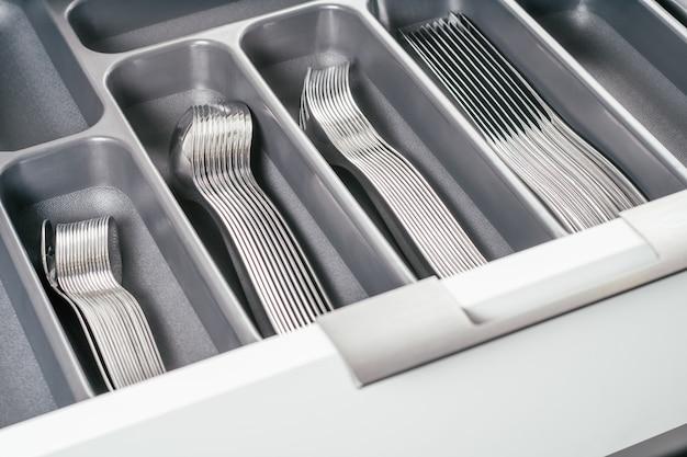 Weiße offene schublade des küchenschranks mit schwarzem besteck-organizer-tablett mit silbernen gabeln, löffeln und messern. küchenaufbewahrungssystem