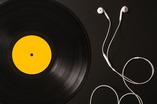 Weiße ohrtelefone und vinylaufzeichnung auf schwarzem hintergrund