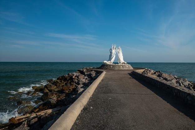 Weiße oktopus-skulpturenstatue am cha-am-fischerhafen im sonnigen tag gegen bewegungsseewelle und blauen himmel, phetchaburi-provinz, thailand.