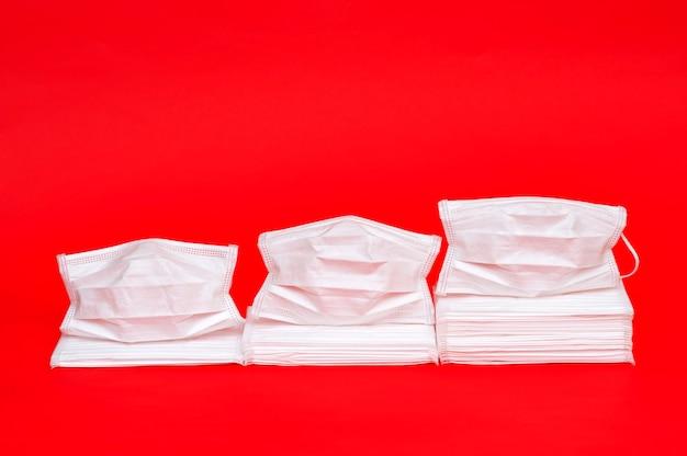 Weiße operationsmasken auf rot. statistisches konzeptdiagramm, das den erhöhten verbrauch von masken zeigt