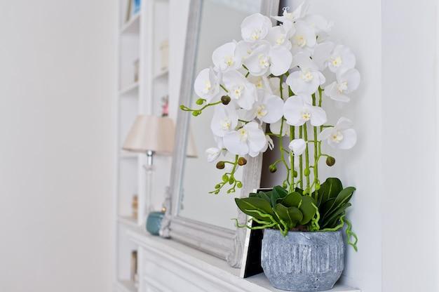Weiße orchidee in einem topf auf dem kamin.
