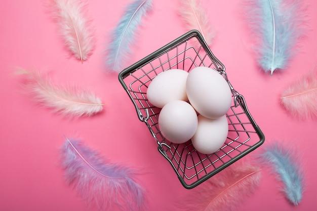 Weiße ostereier in einem einkaufskorb, einkaufswagen, mehrfarbige zarte vogelfedern auf einem rosa hintergrund