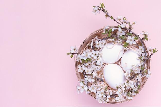 Weiße ostereier in einem korb mit blumen auf einem rosa hintergrund.