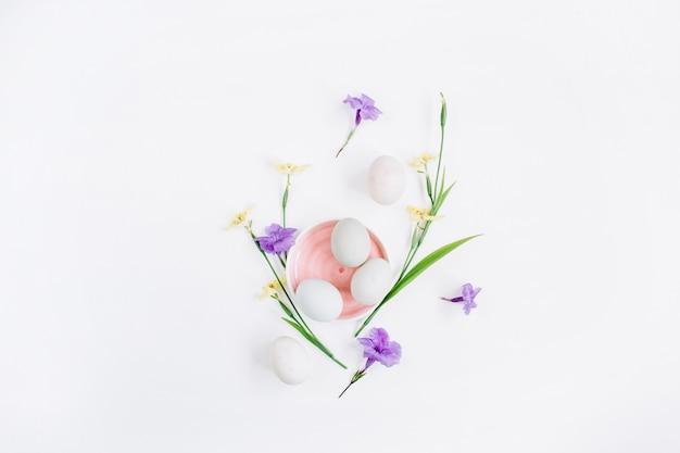 Weiße ostereier in rosa platte mit gelben und lila blüten auf weißer oberfläche