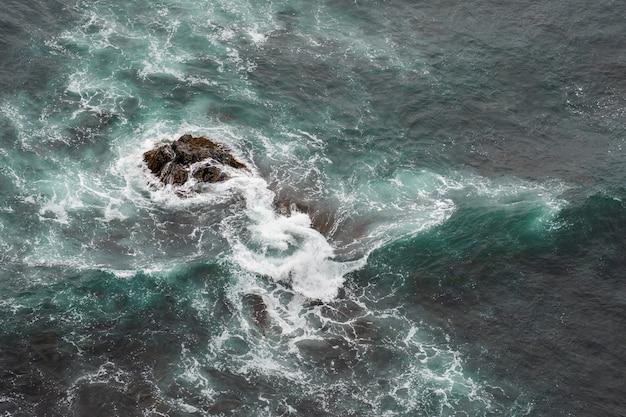 Weiße ozeanwellen, die im sommer über küstenmeerfelsen abstürzen.
