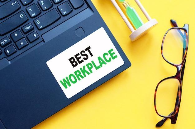 Weiße papierkarte mit text best workplace blatt weißes papier für notizen, taschenrechner, sanduhr, gläser im weißen hintergrund. geschäftskonzept. gelber hintergrund.