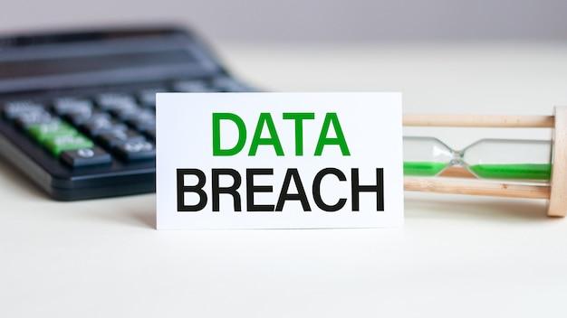 Weiße papierkarte mit text data breach blatt weißes papier für notizen, taschenrechner, sanduhr in der weißen wand. unternehmenskonzept.