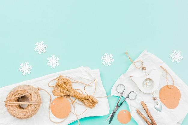 Weiße papierschneeflocke; jutefaden; papier; schere und stick für die herstellung von wandbehang schaustück auf türkisfarbenen hintergrund