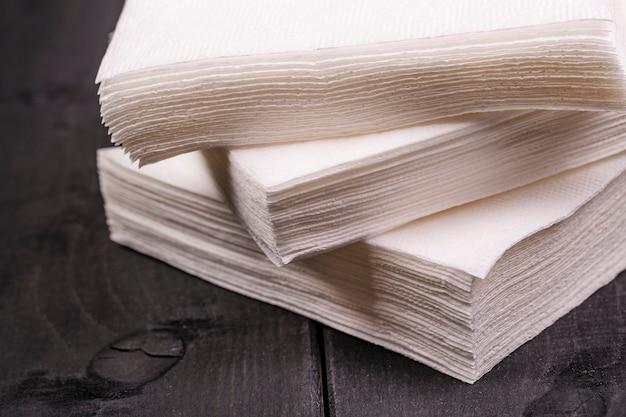Weiße papierserviette auf altem schwarzem holztisch