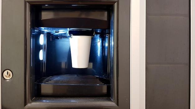 Weiße papiertasse im fenster einer automatenkaffeemaschine. der prozess der kaffeezubereitung in einer watmaschine.