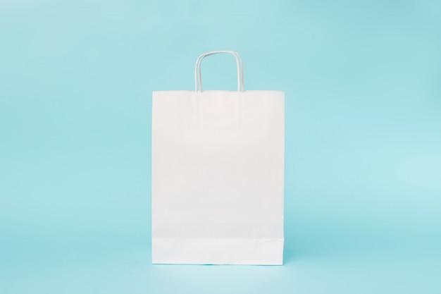 Weiße papiertüte auf blauem hintergrund.