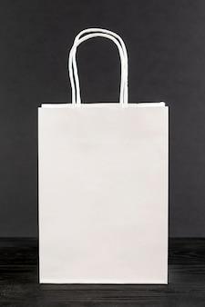 Weiße papiertüte auf schwarzem hintergrund