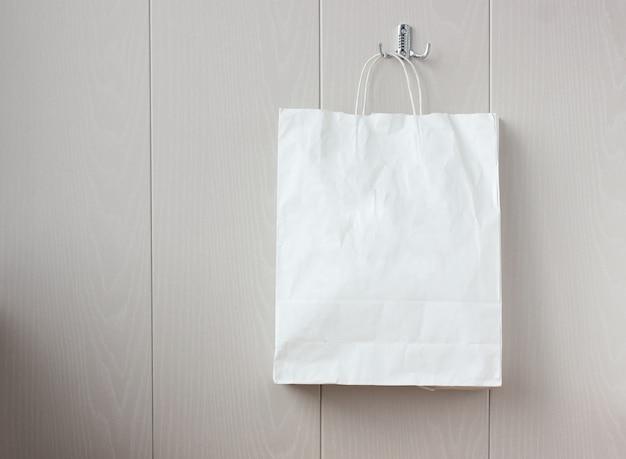 Weiße papiertüte, die an einer hellen wand hängt