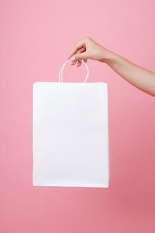 Weiße papiertüte unter dem logo in den händen des mädchens auf einem rosa raum. shopping mock up holding