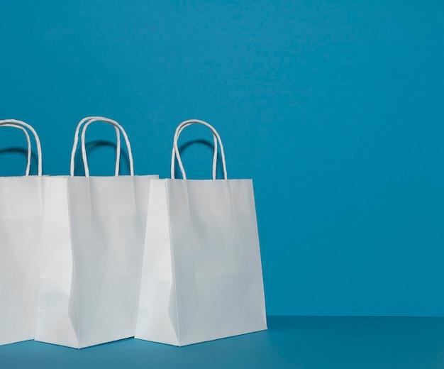 Weiße papiertüten auf einem hellblauen kopierraumhintergrund. wiederverwendbare einkaufstaschen.
