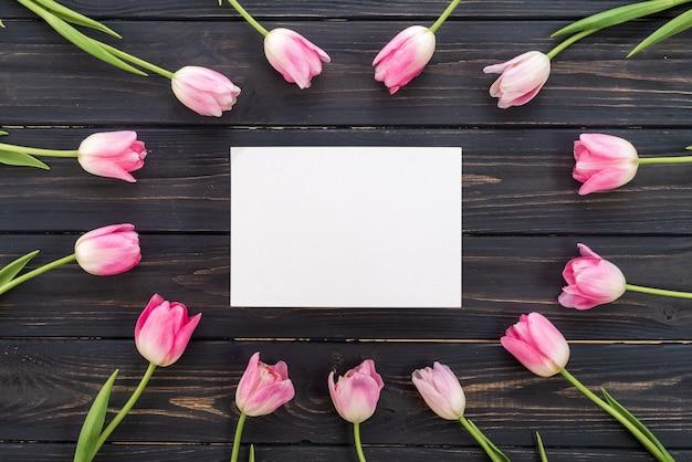 Weiße pappe mitten in rosa tulpen. frühlingskonzept