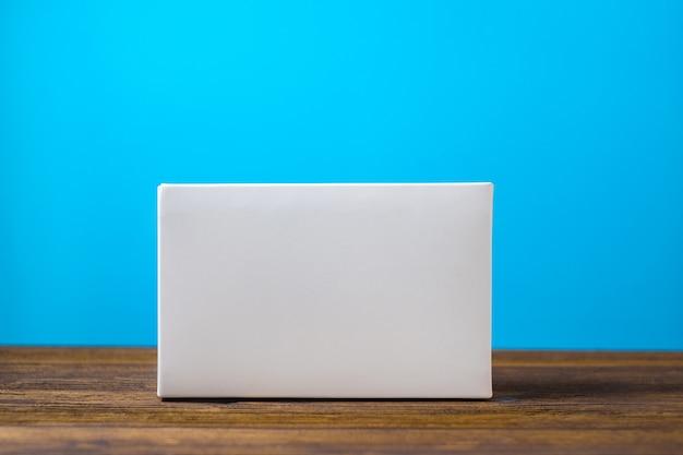 Weiße pappschachtel des leeren pakets auf holz