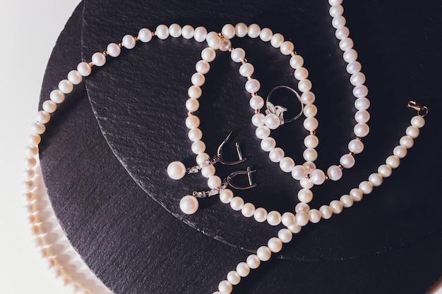 Weiße perlenkette auf einer schwarzen seidennahaufnahme.